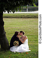 Newlywed couple kissing under tree in park outdoors