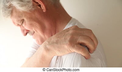 man with shoulder pain - senior man flexes and massages his...