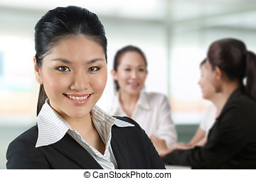Asian business woman with her team in background.