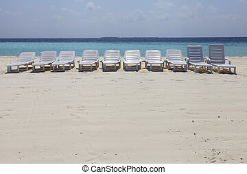 Empty Beach - Empty beach with recliners all lined up for...
