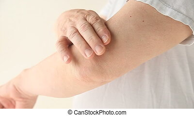 elbow pain - a man checks the soreness in his elbow