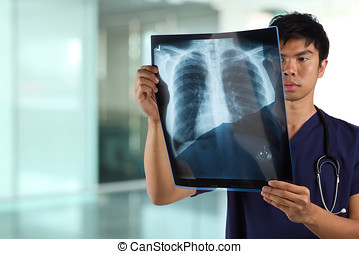 Asian Male nurse looking at X-ray - Asian healthcare worker...