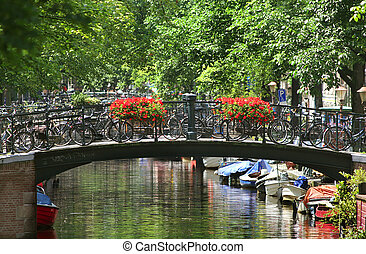 Amsterdam cityscape - View on small bridge with flowers and...