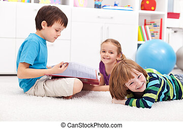Kids reading a book and having fun