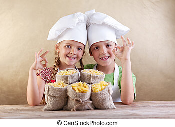 Kids with chef hats and pasta varieties - traditional food -...