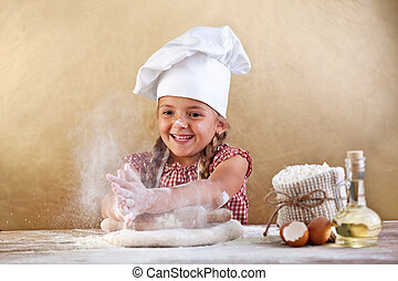 Making the dough for pizza is fun - little chef playing with...