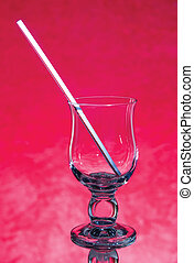 empty glass with a straw on a red background - abstract...