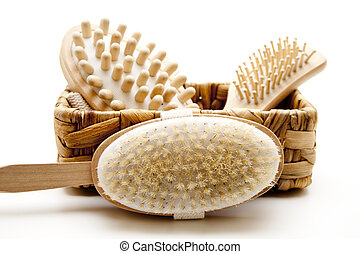 Massage and hairbrush in the basket on white background