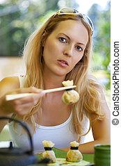 woman with chopsticks at japanise cafe - Young beautiful...