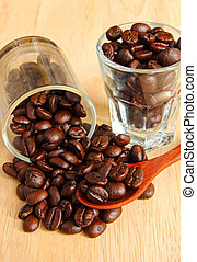 Coffee beans in glasses with spoon on wooden background