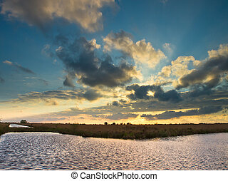 Colorful cloudy sky above dutch wetland nature reserve
