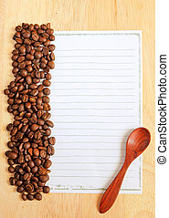 Coffee beans and spoon with paper for notes on the wooden background