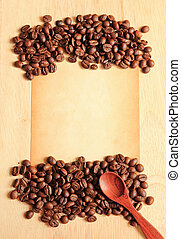 Coffee beans and spoon with old paper on the wooden background