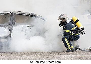 firefighters crouch - a firefighter putting out a fire
