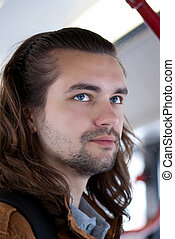 Young sexy attractive guy with long hair and blue eyes
