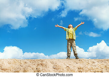 Happy child standing on the top with hands raised up. Happiness and freedom concept.