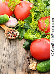 Vegetables for pickling on a wooden table - Tomatoes,...