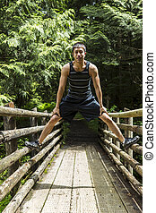 Athletic Young Man on Wooden Bridge