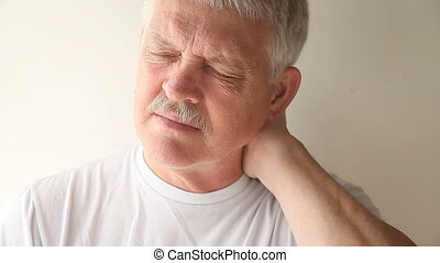 man with a sore neck - senior man experiencing pain and...