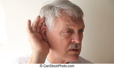 senior man cannot hear - an older man strains to hear what...