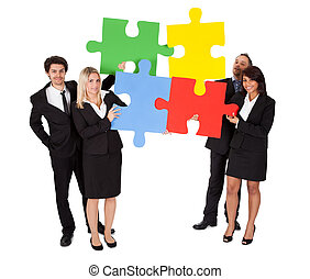 Group of business people assembling puzzle - Group of...
