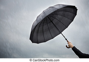 umbrella protection concept - rain and hand of man with...