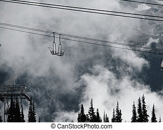 ski lift chairs meet in the clouds - Two empty ski lifts...