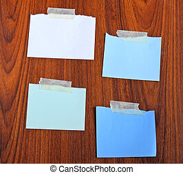 Notepaper attach with tape on wooden background