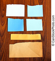 Ripped notepaper on wooden background