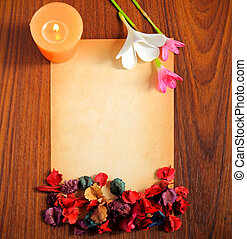old paper with dry flower and candle on wooden background