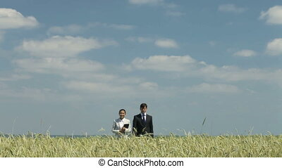 Prosperity - Young business people walking across the wheat...