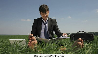 Business on the grass - Cheerful businessman sitting on the...