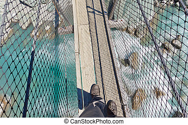 Boots on swing bridge over troubled white water - Booted...