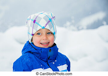 Winter boy throwing snowball - Smiling happy boy having fun...