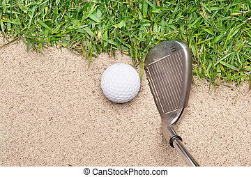 Golf club and ball - A golf ball in a sand trap getting...