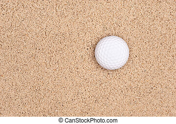 Golf ball in sand - A lone golf ball in a sand trap looking...