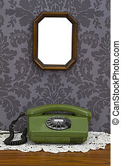 Old fashioned telephone and wooden frame on decorative...