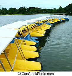 Yellow and blue water-cycle boat in park - Yellow and blue...