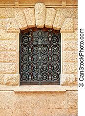 Ironwork - Decorative ironwork window at old stone house
