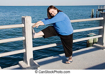 Stretching for Fitness - Beautiful plus-sized woman...