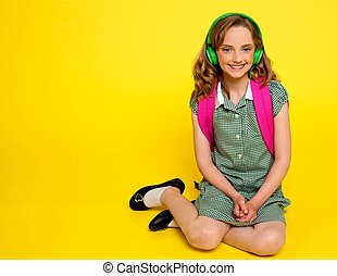 Pretty girl kid listening to music. Seated on floor