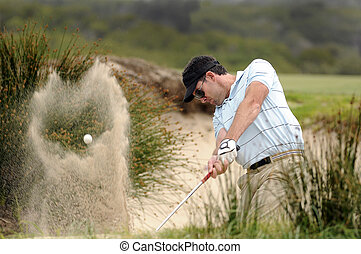 Golfer playing a bunker shot - Golfer hitting a bunker shot