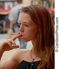 smoking girl - young woman smoking a cigarette in a city:...