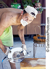 man working with Electrical saw - Young dirty man working at...