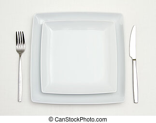 Dinner place setting. white square china plates with silver fork and knife