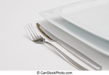 Dinner place setting. white  plates with silver fork and knife