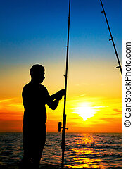 Fishermen boy fishing at beautiful sunset