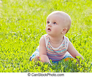 Little baby sitting on the grass in park