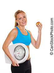 woman with bathroom scale and apple - young woman with...