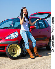 woman with a flat tire on car